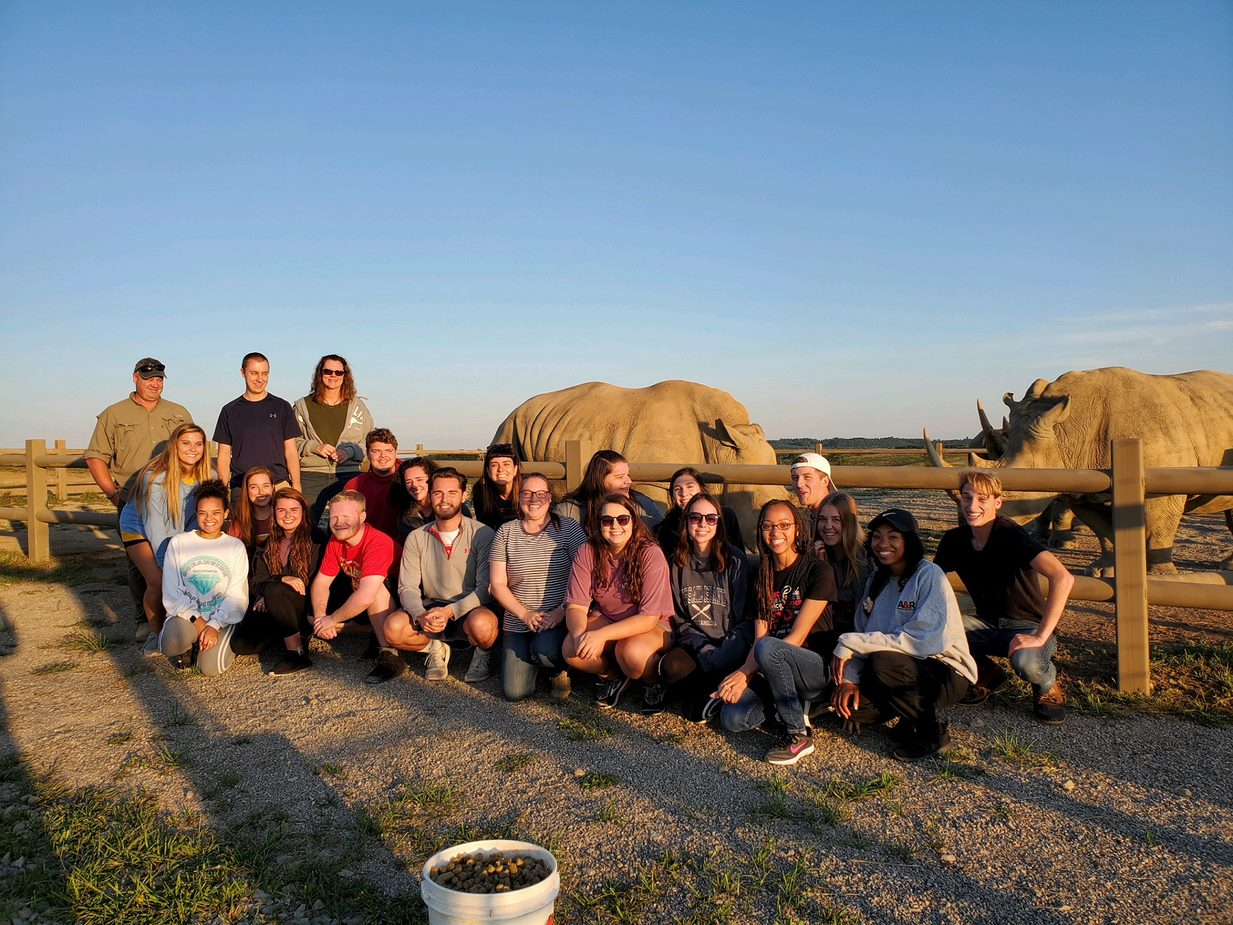 Group photo of students in front of rhino pen at the Wilds