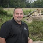 Photo of Adam with lion laying on rock in the background